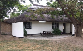 Thatched chalet with private garden and outside seating area.